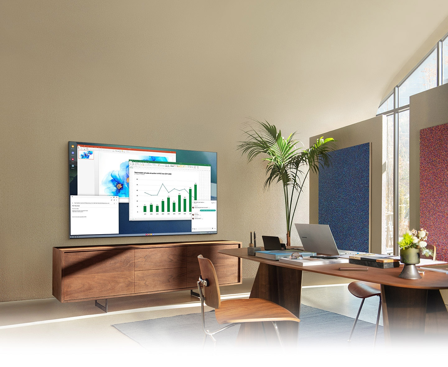 In a living room home office, QLED TV screen shows PC on TV feature which allows home TV to connect to office PC.