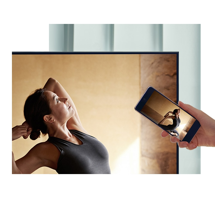 A user taps their smartphone against their QLED TV to mirror their ballerina contents to a bigger screen for more comfort.