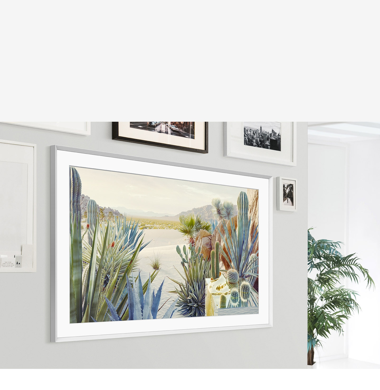 The Frame is mounted on the wall of a home interior and its modern frame design blends with the other picture frames on the wall.