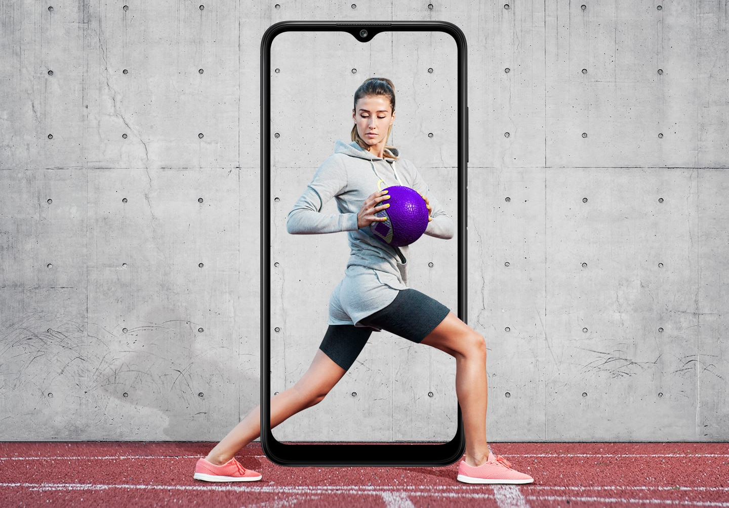 A woman is shown performing a standing torso twist with her legs in a lunge position while holding a purple medicine ball. The Galaxy A03s's slim bezel frames her entire body, with her feet and part of her calf outside it.