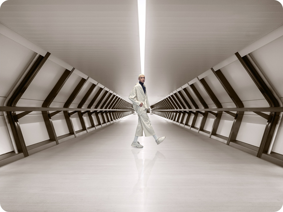 A man standing in a corridor, and with the Ultra Wide Camera, much more corridor can be taken in the shot.