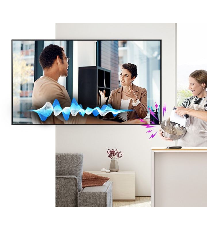 A woman is cooking while watching TV. Despite the noise coming from the mixer, the Active Voice Amplifier technology makes it easy to hear TV conversations.