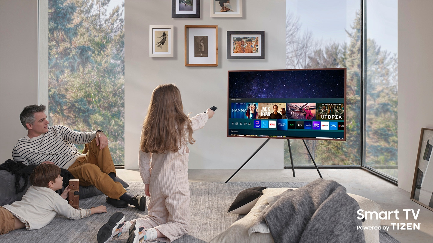 A father and his two children are enjoying The Frame which is mounted to Studio Stand. On the screen is the Universal Guide user interface menu which the girl is controlling with One Remote. The Smart TV Powered by Tizen logo is visible.