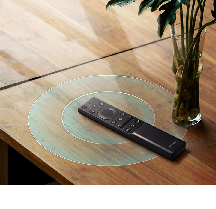 Simulated battery charging wave graphics are beneath the Samsung One Remote to illustrate that it is recharging from indoor lighting.