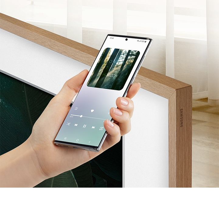 A mobile device which is playing music is being held very close to The Frame.