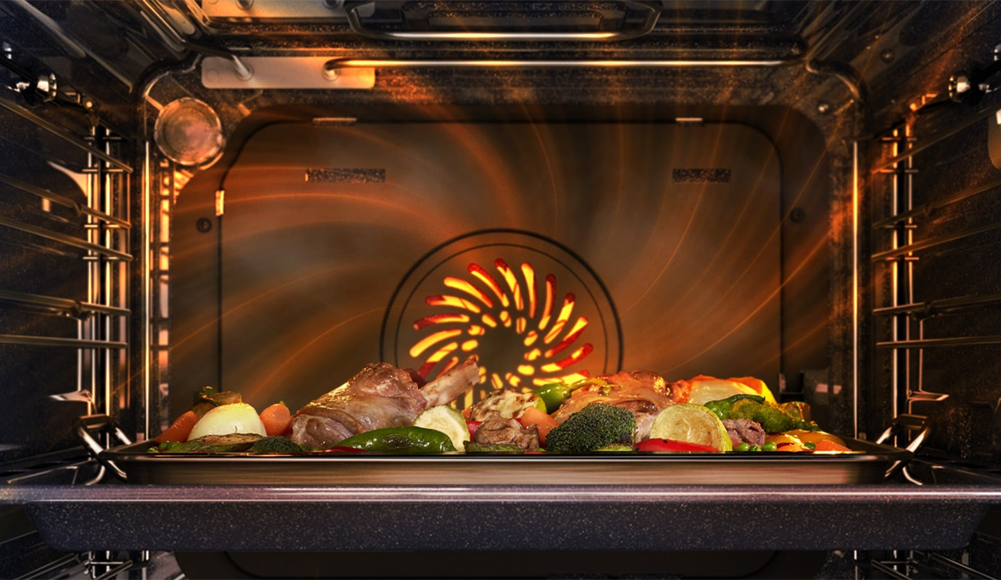 Shows a meal being cooked inside the oven with a heated fan at the back spreading heat evenly all around the oven.