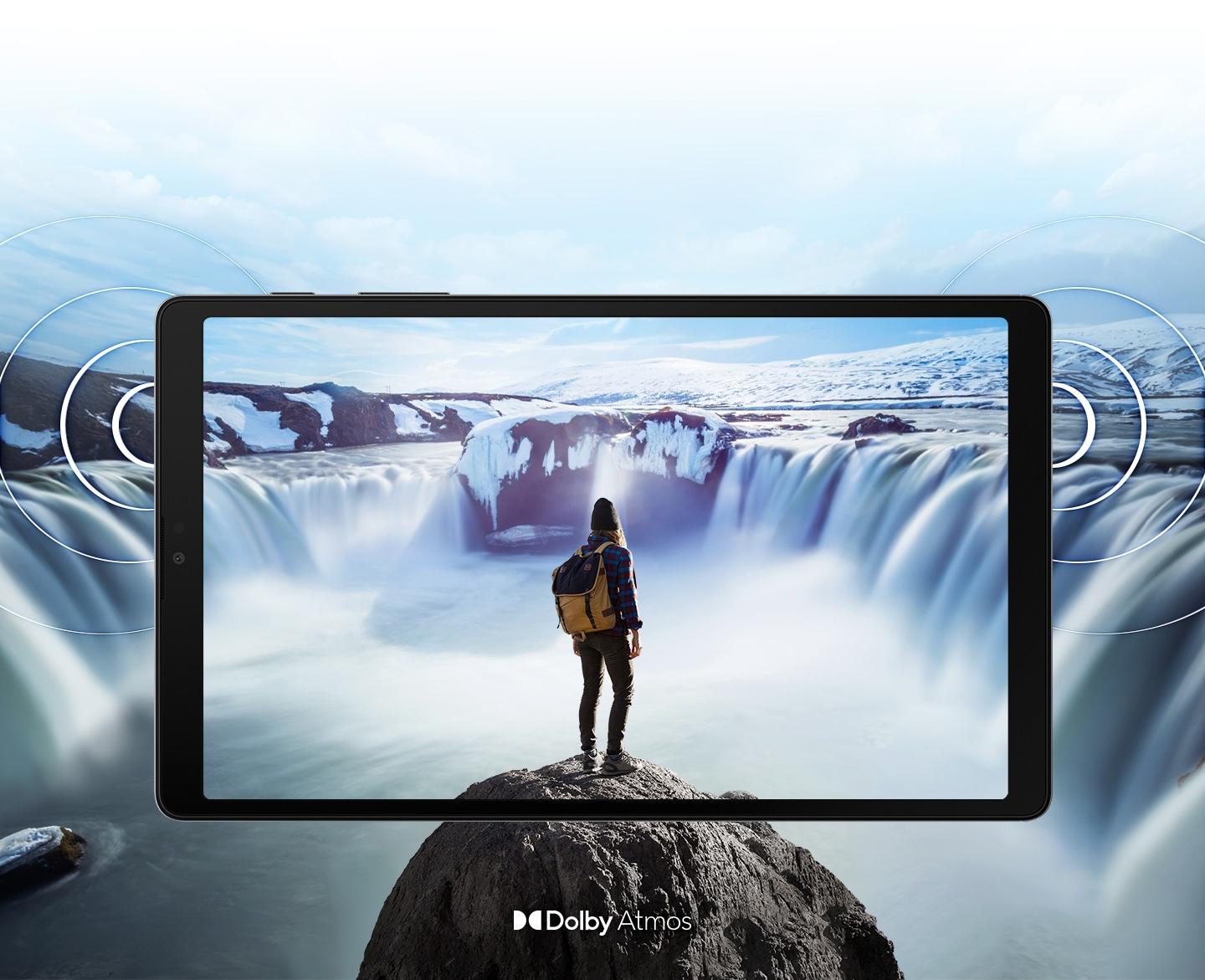 Galaxy A7 Lite seen from the front with an image of a person standing on a rock in front of steaming waterfalls on either side onscreen. The image expands past the edges of the tablet to show the expansiveness of the display. Rings come out from the sides to demonstrate the location of the dual speakers and the immersive sound of Dolby Atmos.