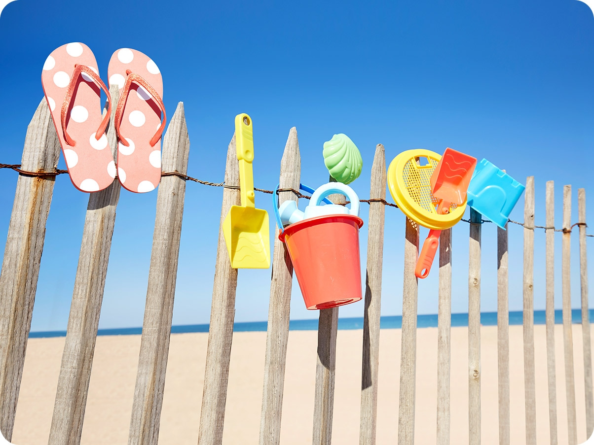 2. Beach toys are drying on a wooden fence. With Ultra Wide Camera, you can see more toys and the beach in the background.