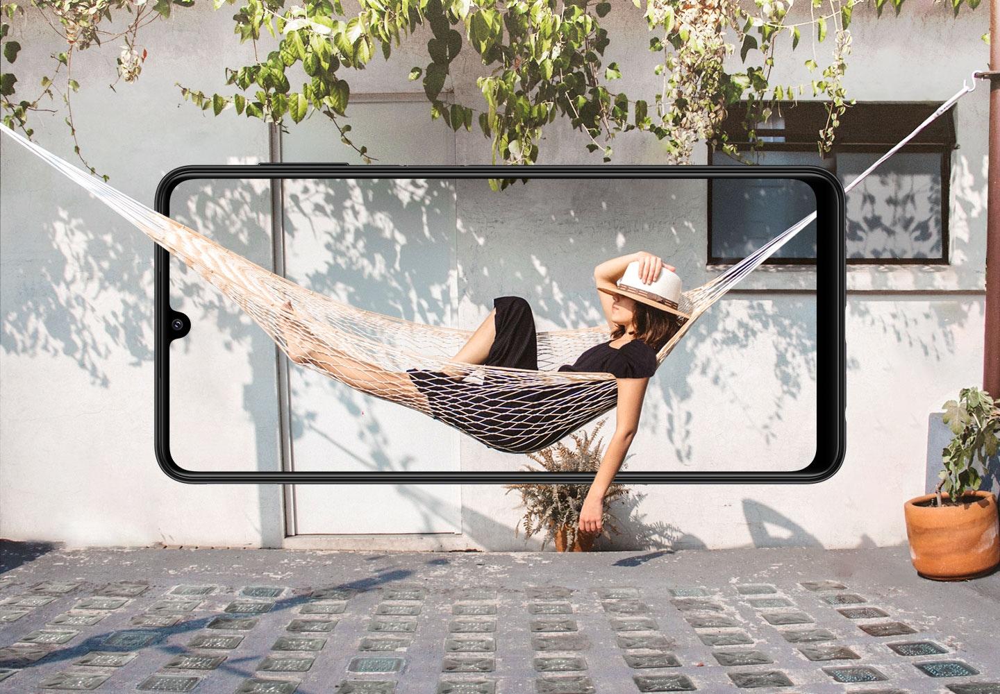 A Galaxy A22 is seen from the front, horizontally. Onscreen, a woman rests in a hammock, which blends beyond the bezel with the side of a house.