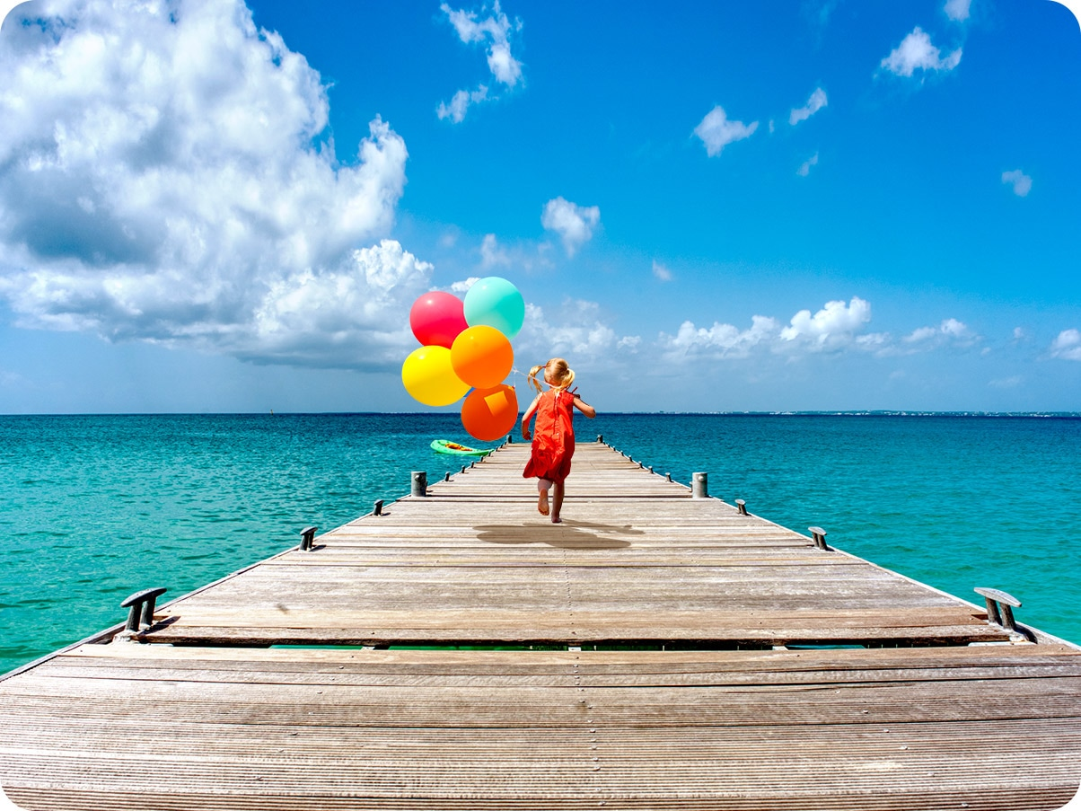 A girl is running on a dock holding a bundle of balloons. With Ultra Wide Camera, you can see more of the dock and the ocean.