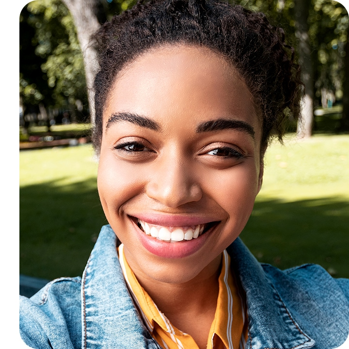 Selfie of a young smiling woman looking into camera lenses, with a little bit of green grass and tree shown in the background