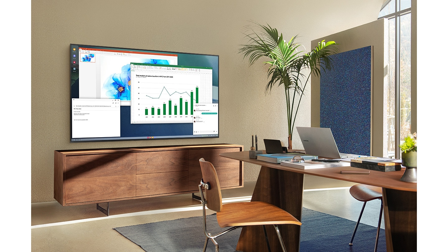 In a living room home office, A TV screen shows PC on TV feature which allows home TV to connect to office PC.