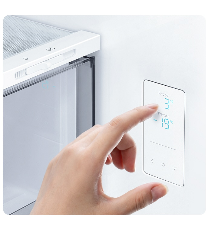 A hand touches the LED screen inside the fridge, with water and ice controls, and temp settings for the fridge and freezer.