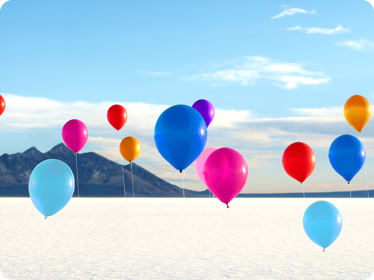 Colorful balloons float in the air against a snow-covered field and beautiful blue sky in the background.