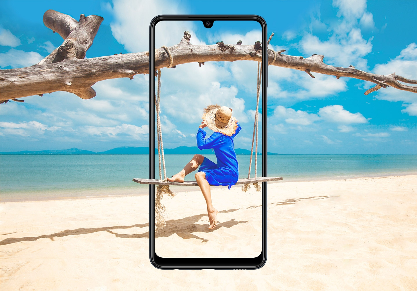 A Galaxy M22 is seen from the front, vertically. Onscreen, a woman sits on a wooden swing hanging from a branch, which blends beyond the bezel with the sandy beach.