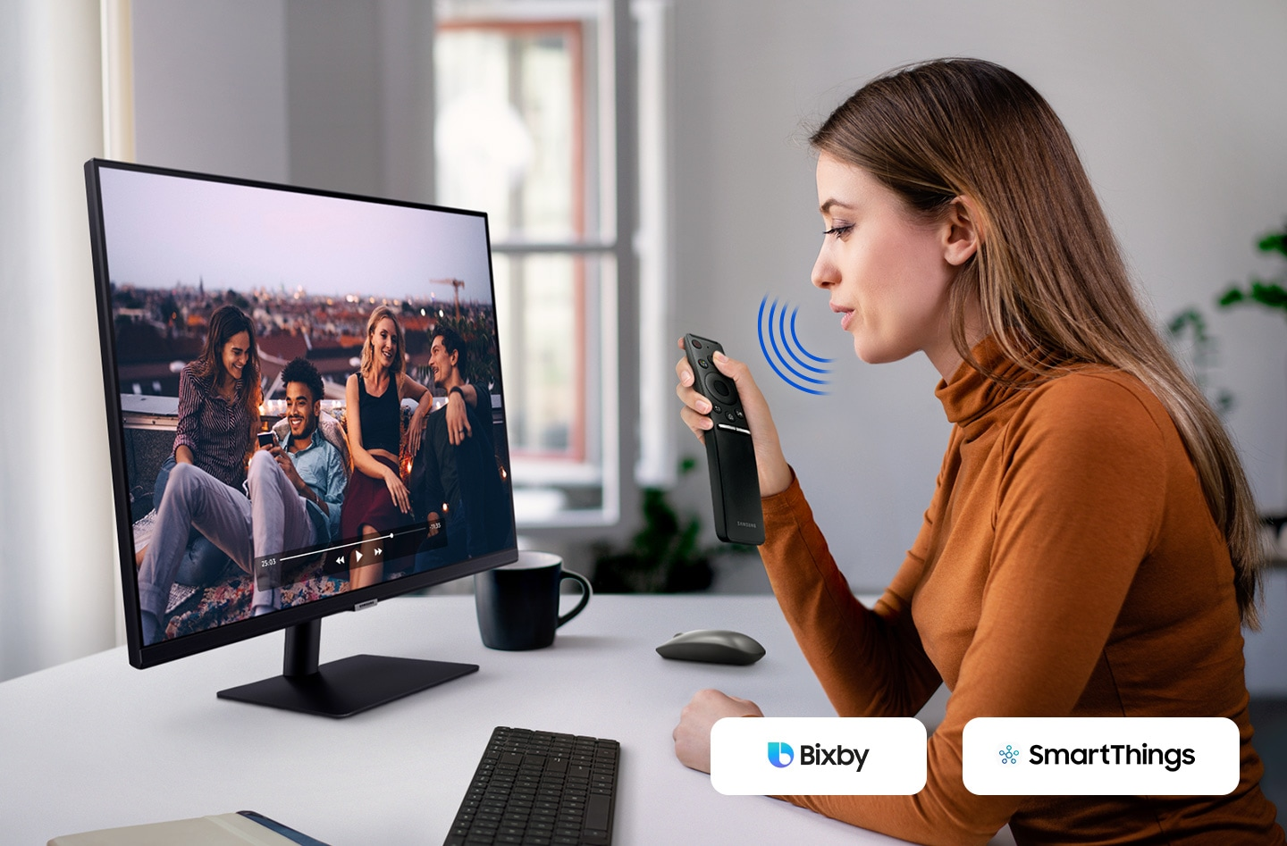A woman speaks to the monitor. And a video is played on it. The Bixby and SmartThings icon is in the right corner.
