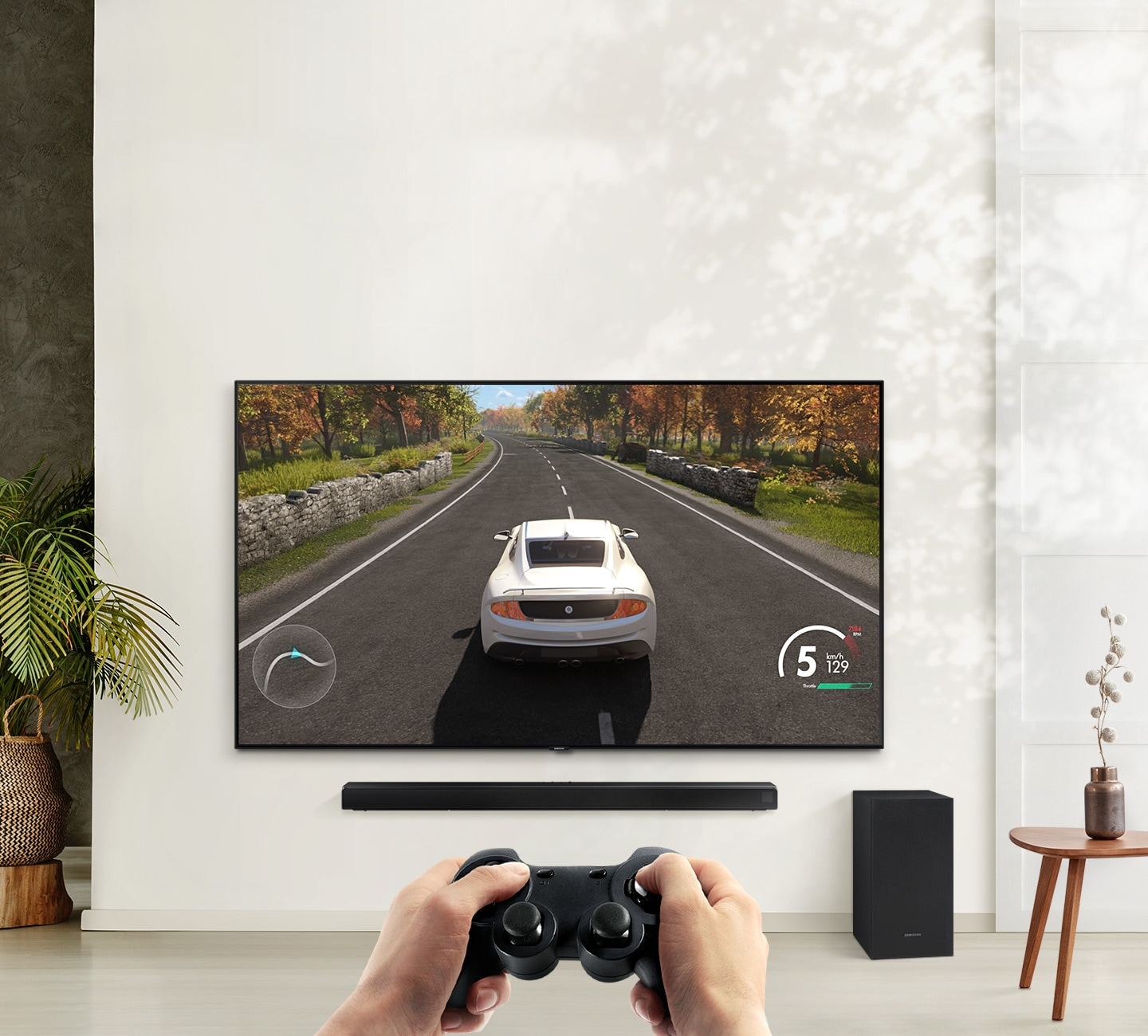 A user is enjoying soundbar's Game Mode while playing a racing game on their TV connected to soundbar and subwoofer.