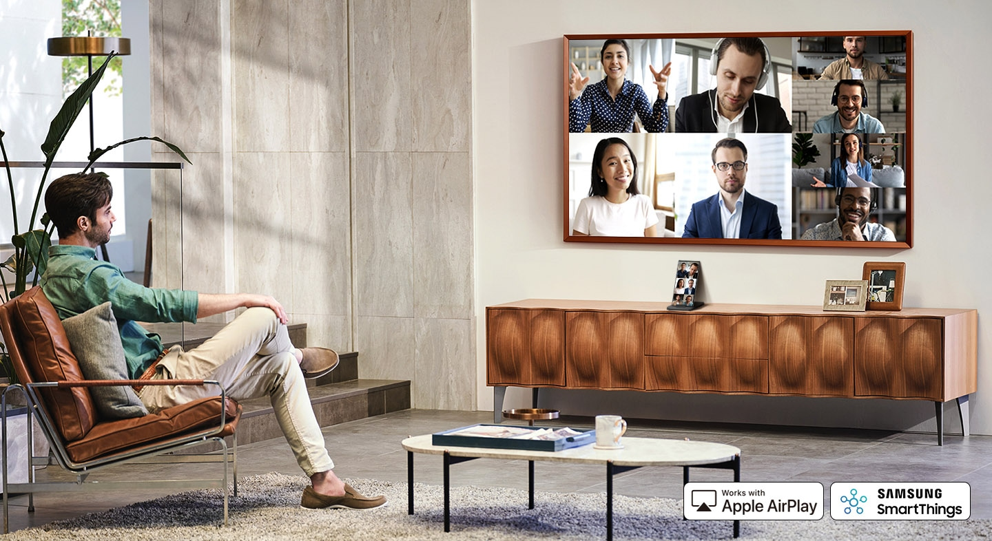 A man is in a living room and using his TV screen to video chat with various people. Beneath his TV is his smartphone device which shows the same video chat. The logo for Samsung SmartThings and Works with Apple AirPlay are displayed.