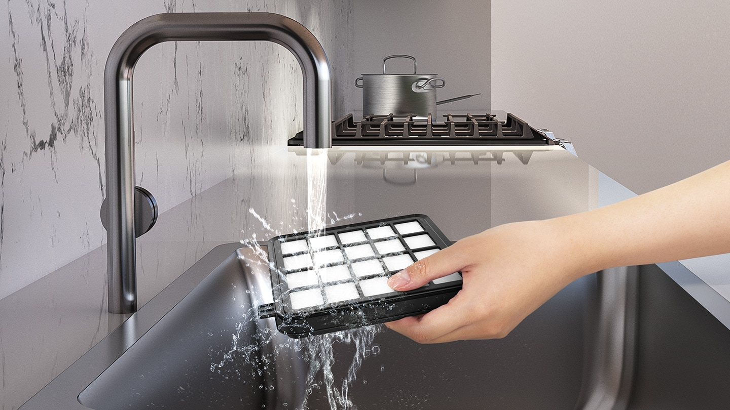 A person washes the filter in the kitchen sink.