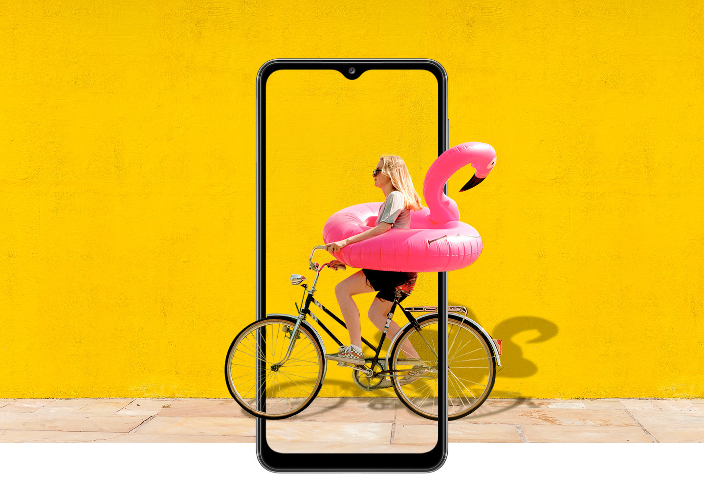 A woman on bike behind Galaxy A32 5G. The picture goes the phone display's edges to represent its immersive view.