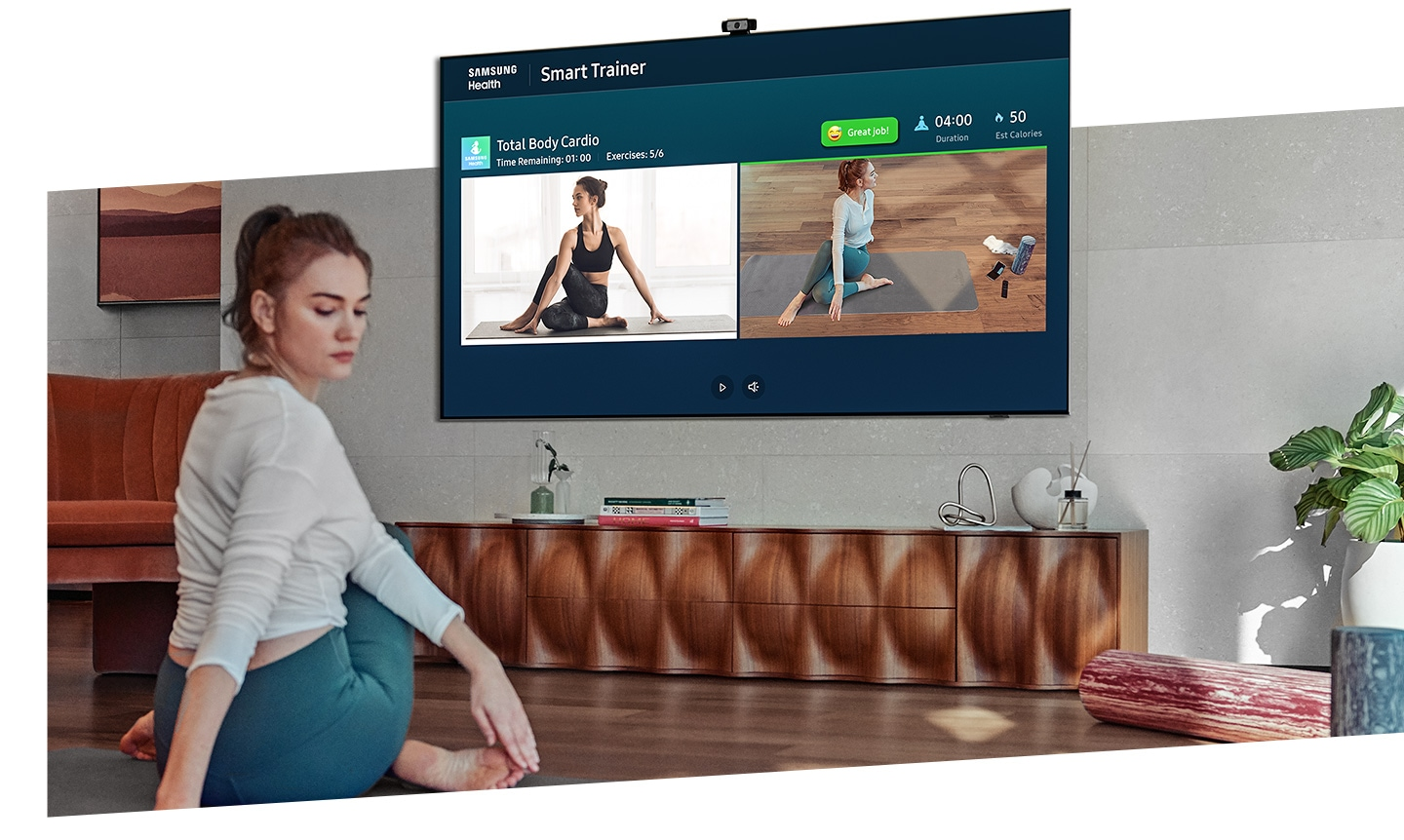 A woman exercises more accurately with QLED TV's camera-powered coaching feature which lets her watch herself and the training coach at the same time.