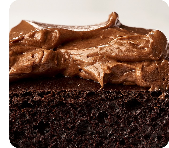 An extreme close-up the cross-section of a chocolate cake, showing the details of the cake's texture and the swirl of the frosting.