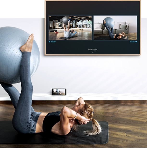 A woman is working out in front of her TV. On the TV screen she can see a screen of herself as well as the screen of the fitness trainer and below the TV her smartphone camera is capturing her workout so she can see it on the TV screen.