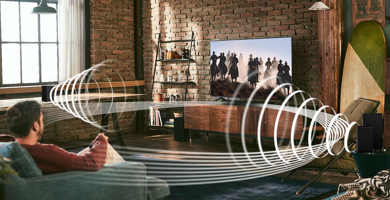 Một người đàn ông thích nội dung đua xe trên TV của mình. Đồ họa Soundwave được phát từ Bộ loa sau không dây và Soundbar của Samsung, thể hiện tính năng Tương thích âm thanh vòm không dây của soundbar Samsung.
