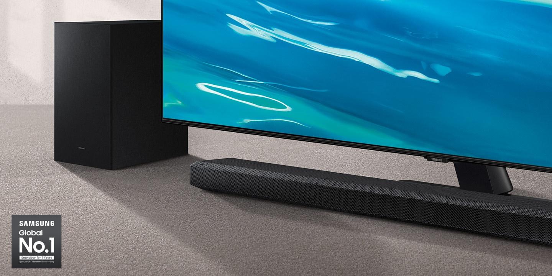 Logo Samsung Global No.1 có thể được nhìn thấy cùng với Soundbar Samsung A700A và loa siêu trầm được đặt bên cạnh TV Crystal UHD.