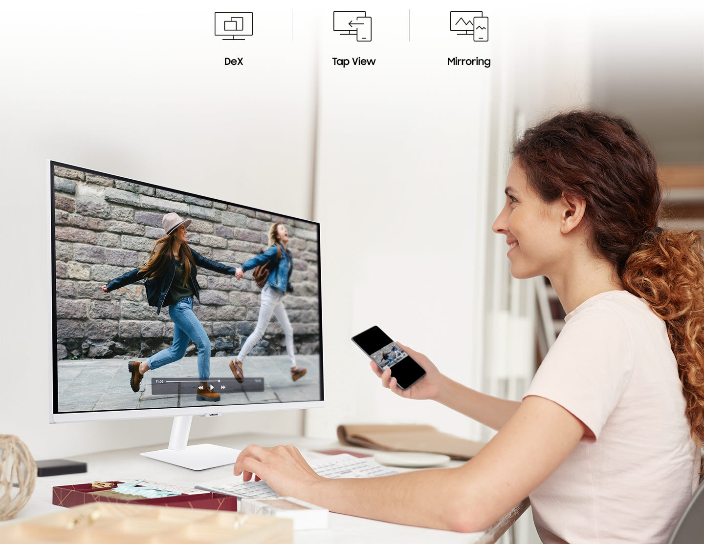 A smiling woman mirrors videos from her phone to her monitor. At the top are the DeX, Tap View, and Mirroring icons.