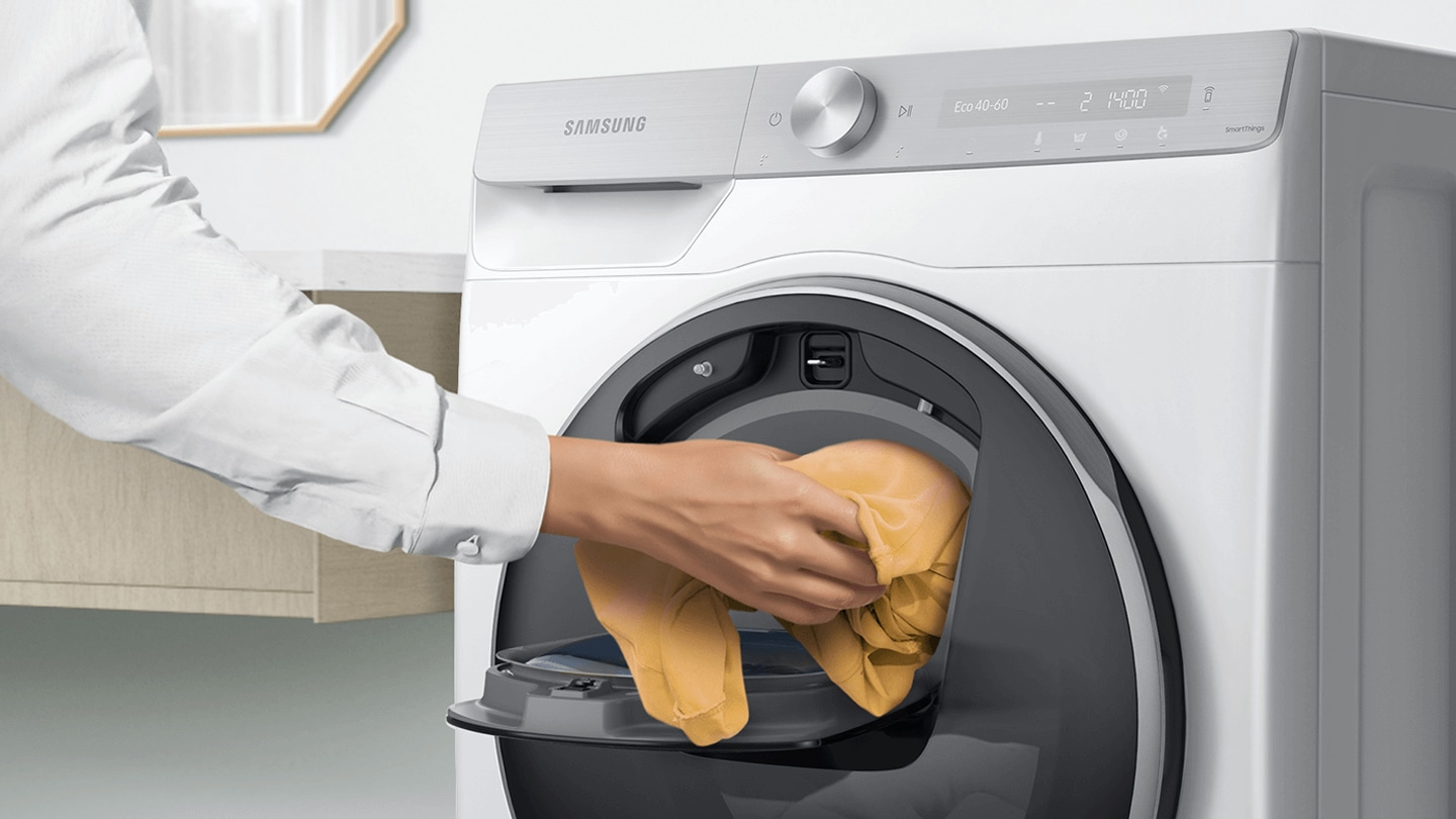 Extra laundry is added into the open Add Wash door by hand.