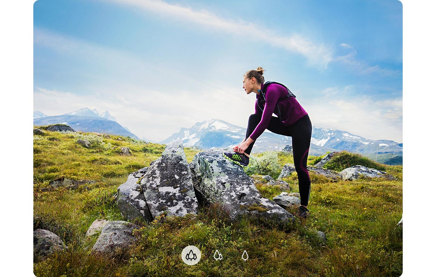 A woman staring at a distance with her foot on a rock and mountains shown in the background, indicating A72 can capture a wider image with Ultra Wide Camera.