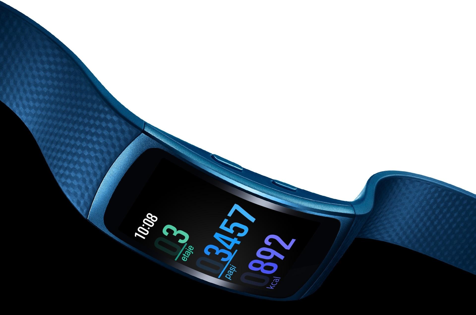 Un dispozitiv Gear Fit2 de culoare albastru, cu ecranul înclinat în jos, arătând cât de ușoară și flexibilă este brățara
