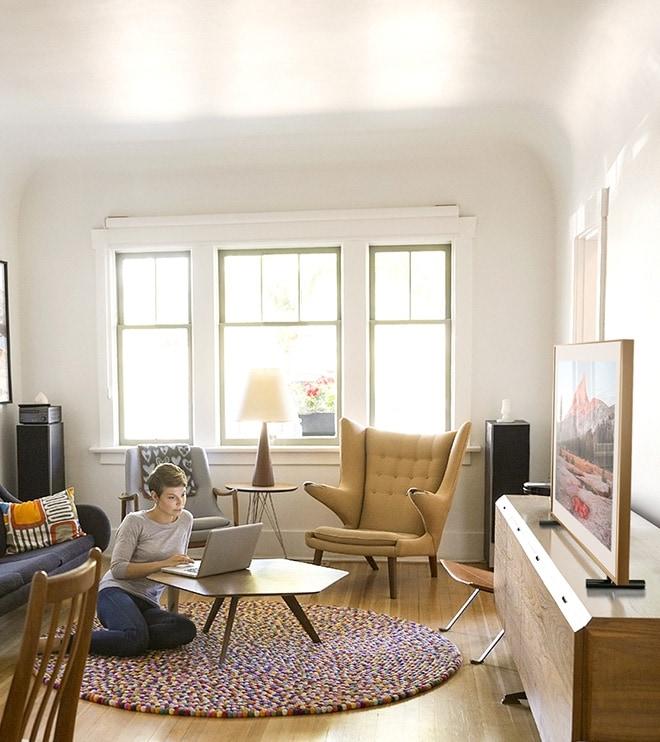 아트레이아웃 모던매트, 매트컬러 엔틱 선택, 여자와 함께 거실의 프레임티비가 보여집니다.