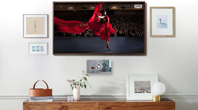 TV모드 흰색 벽면에 액자와 함께 걸려있는 프레임티비 화면 속, 공연중인 여성의 영상이 보여집니다.