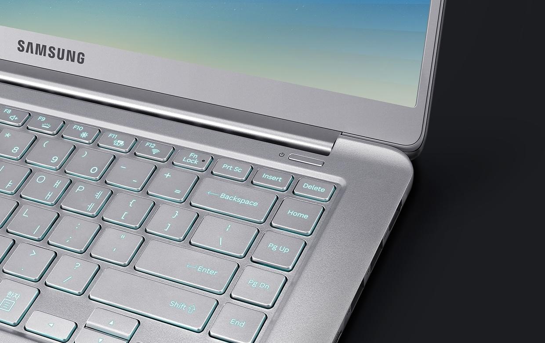 라이트 티탄 컬러 노트북9이 100도 열려 있습니다. 키보드 자판의 우측상단이 보이도록 되어 있고, 자판은 오토 백릿 기능이 적용되어 있어 푸른색을 띄우고 있습니다.