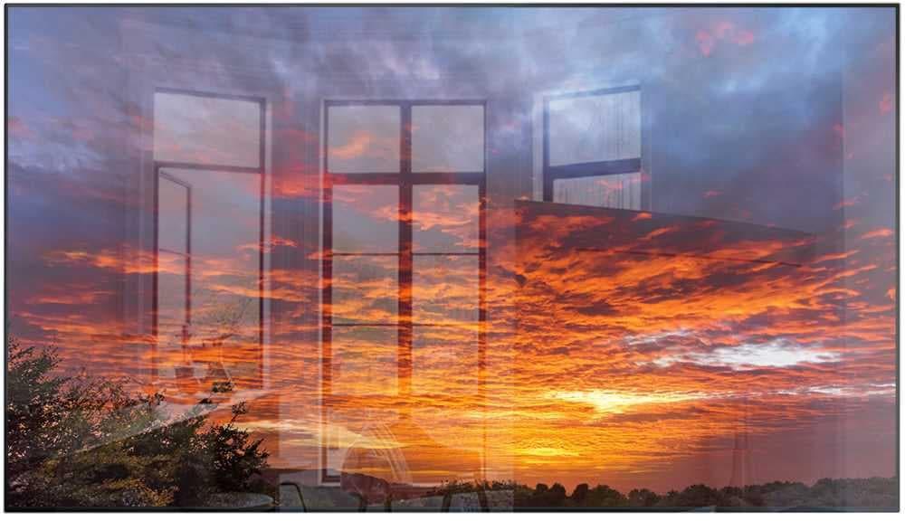 제품의 베젤과 화면만 보여지고 있으며, 화면 안에는 노을진 하늘에 붉은 구름과 파란색 구름이 보여지고 중앙에 가로 선이 있으며 좌측에는 빛이 반사되어 창문이 비추고 있습니다.