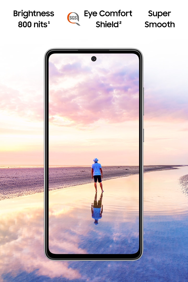 Galaxy A52 5G seen from the front. A scene of a man standing on a beach at sunset with pink and blue colours in the sky expands outside of the boundaries of the display. Text says Super Smooth, Brightness 800 nits and Eye Comfort Shield, with the SGS logo.