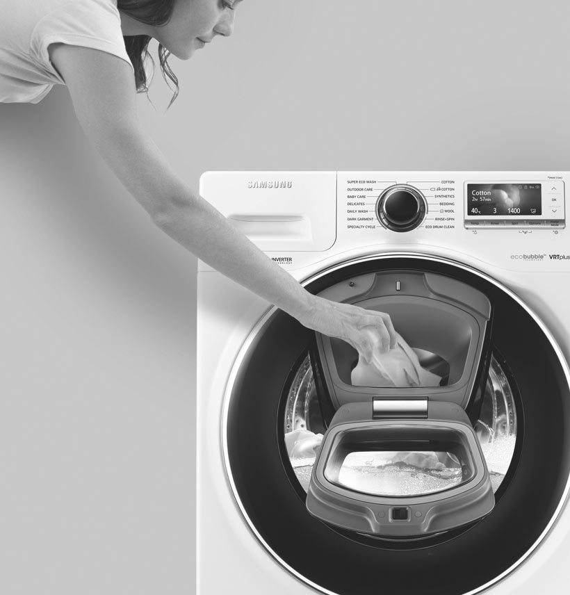 An image showing a woman adding an item to the wash via the Add Door during the rinsing cycle.
