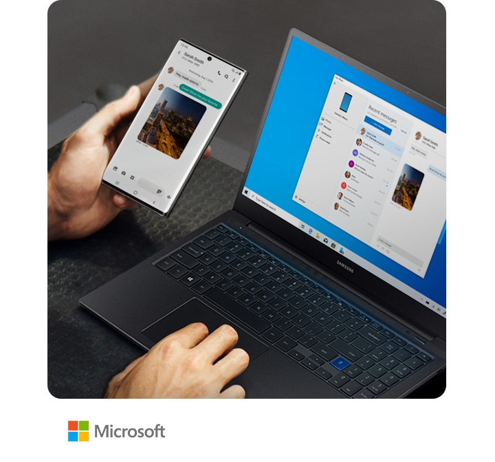 Man working on a laptop and holding Galaxy Note10+. Both the laptop and the phone have the same text message conversation onscreen, showing how Link to Windows syncs messages to your PC.