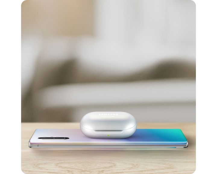 Galaxy Note10+ laying facedown on a table with Galaxy Buds charging on top via Wireless PowerShare.
