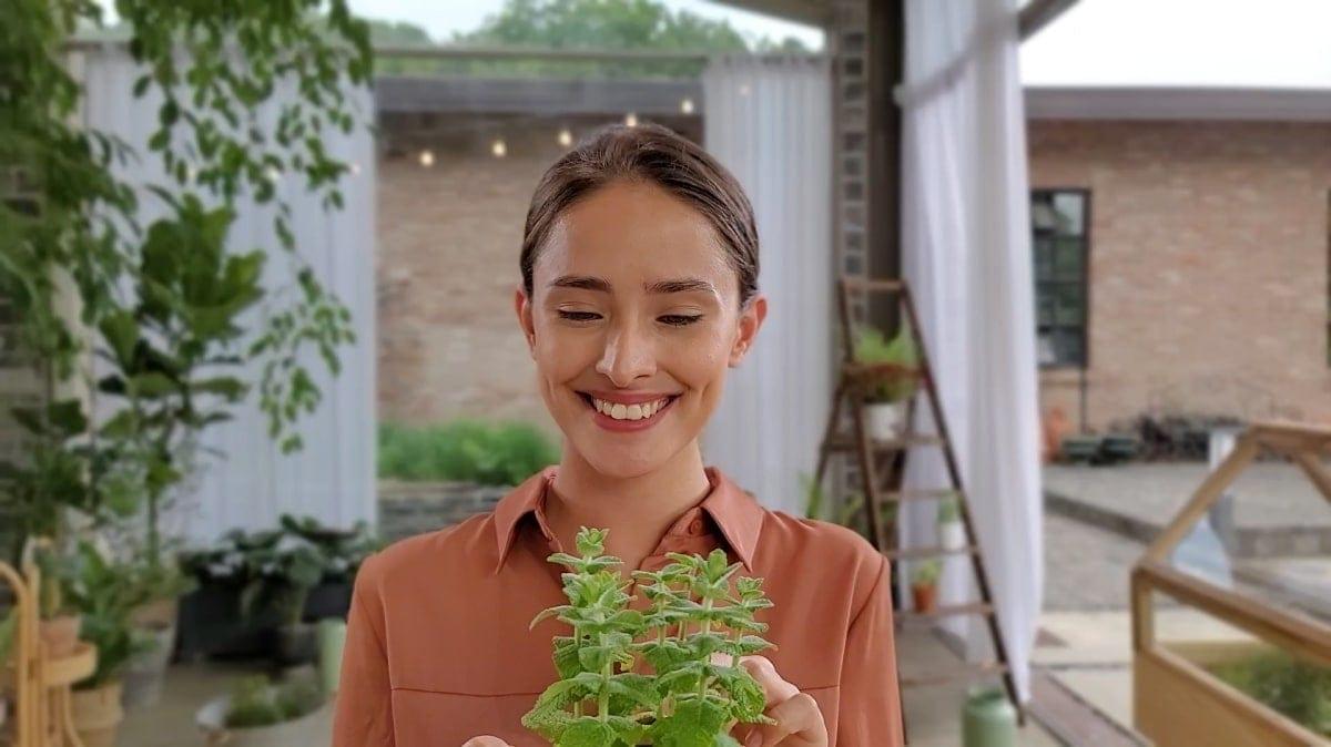 Una mujer cuidando sus plantas, filmada con el filtro Desenfoque en video con Live Focus. El fondo está notablemente suavizado para que la mujer y su planta se destaquen más.