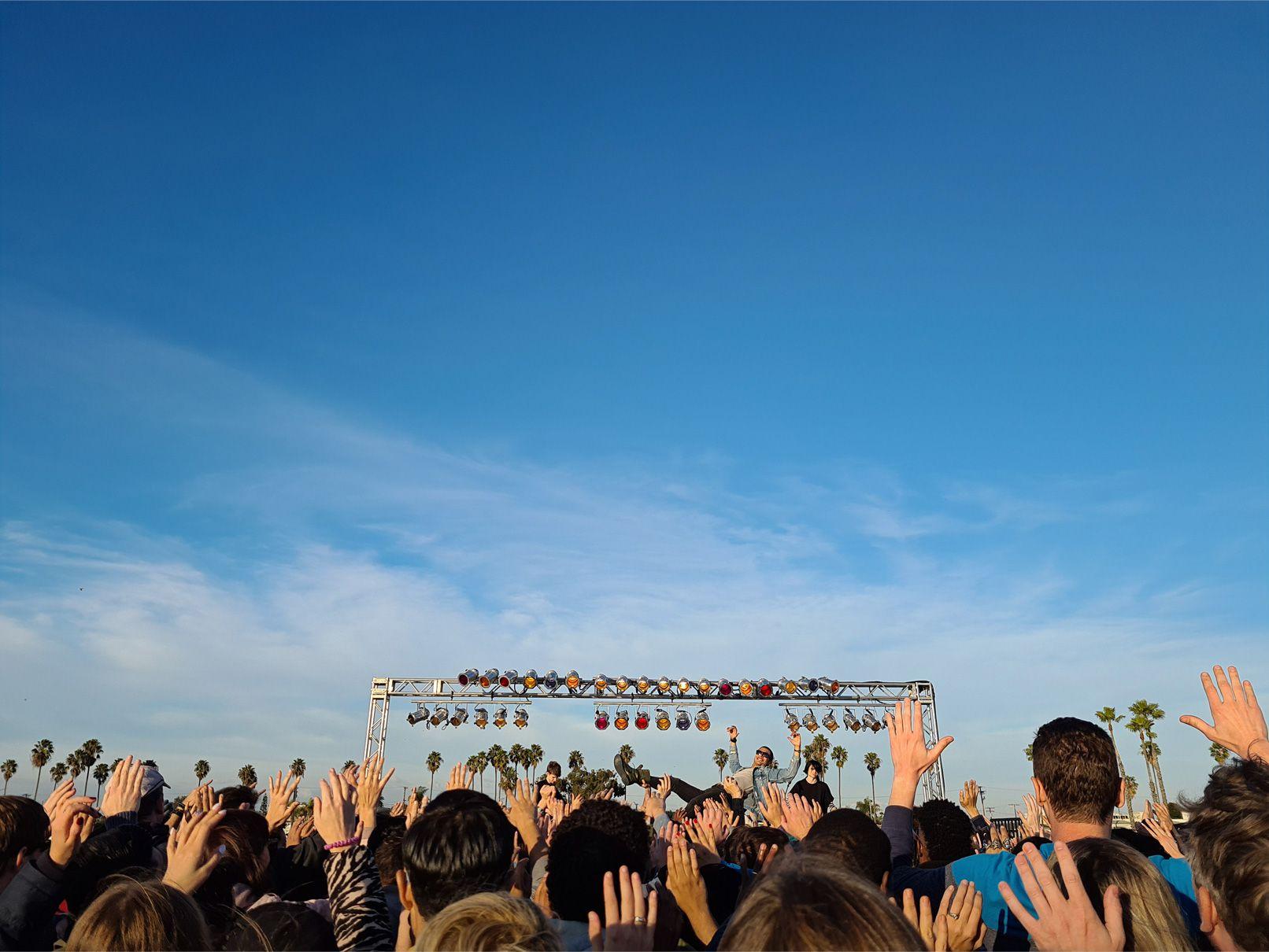 Foto tomada en el Galaxy S20 plus desde el fondo de una audiencia en un concierto al aire libre. Al ampliar la foto con el zoom, vemos un momento divertido de un hombre que pasa por encima de la gente cerca del escenario, mostrando cómo el Zoom Espacial te permite encontrar momentos que de otra manera te habrías perdido