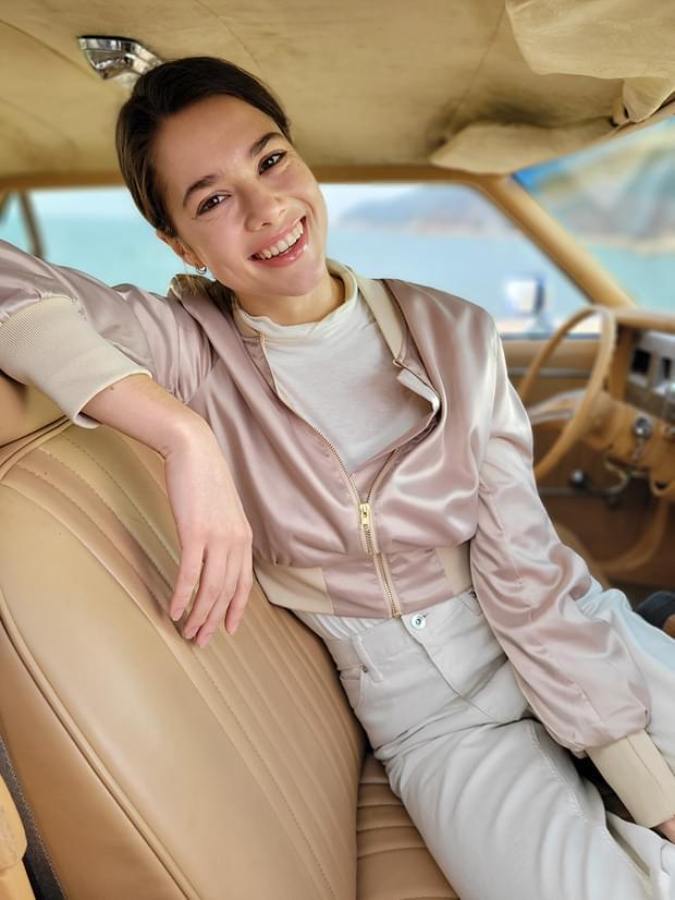 Mujer sentada en el asiento del conductor, tomada en modo Retrato con efecto de Desenfoque aplicado.