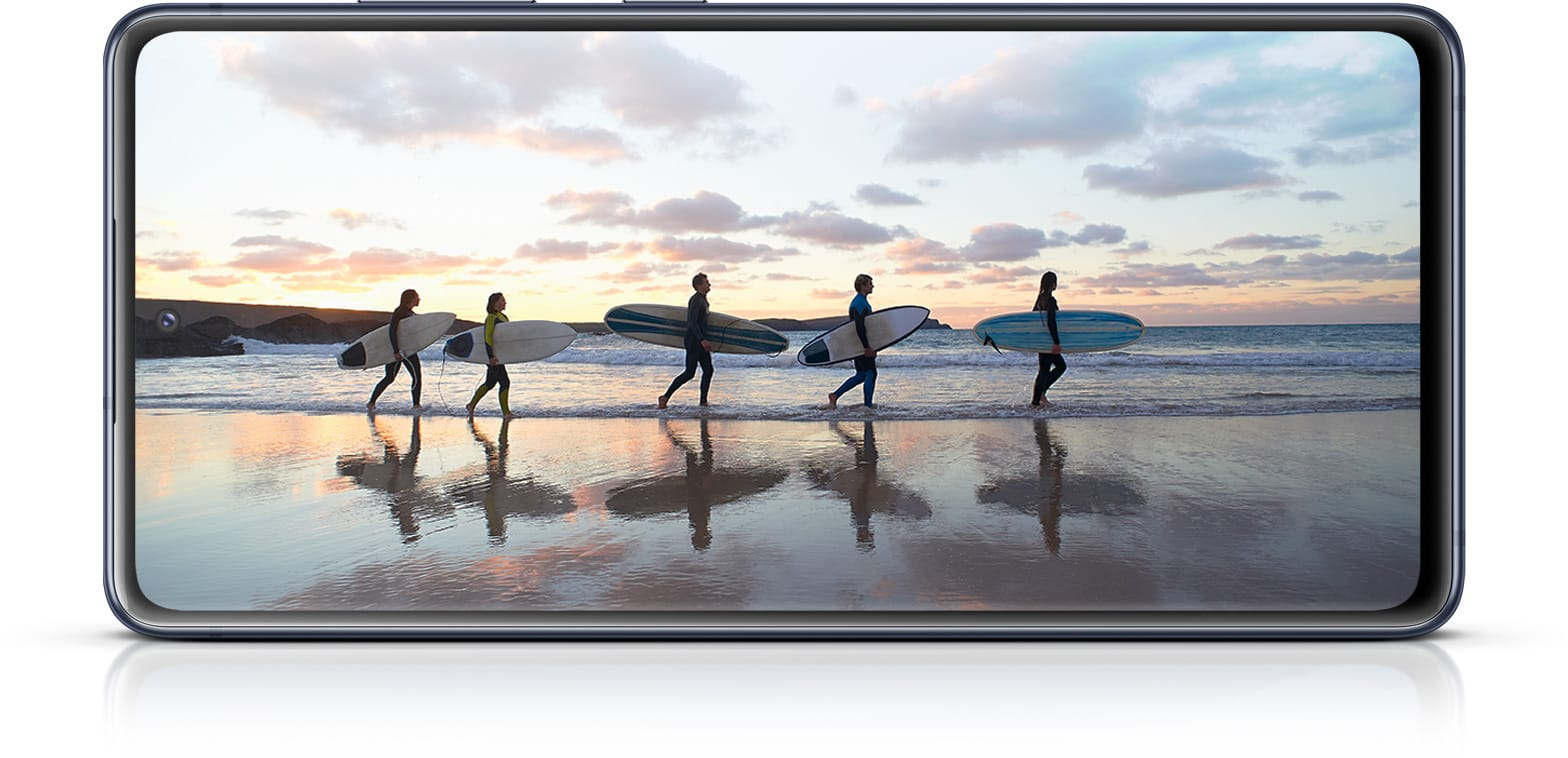 Galaxy S20 FE with a photo of surfers onscreen, showing the immersiveness of the Infinity-O Display.