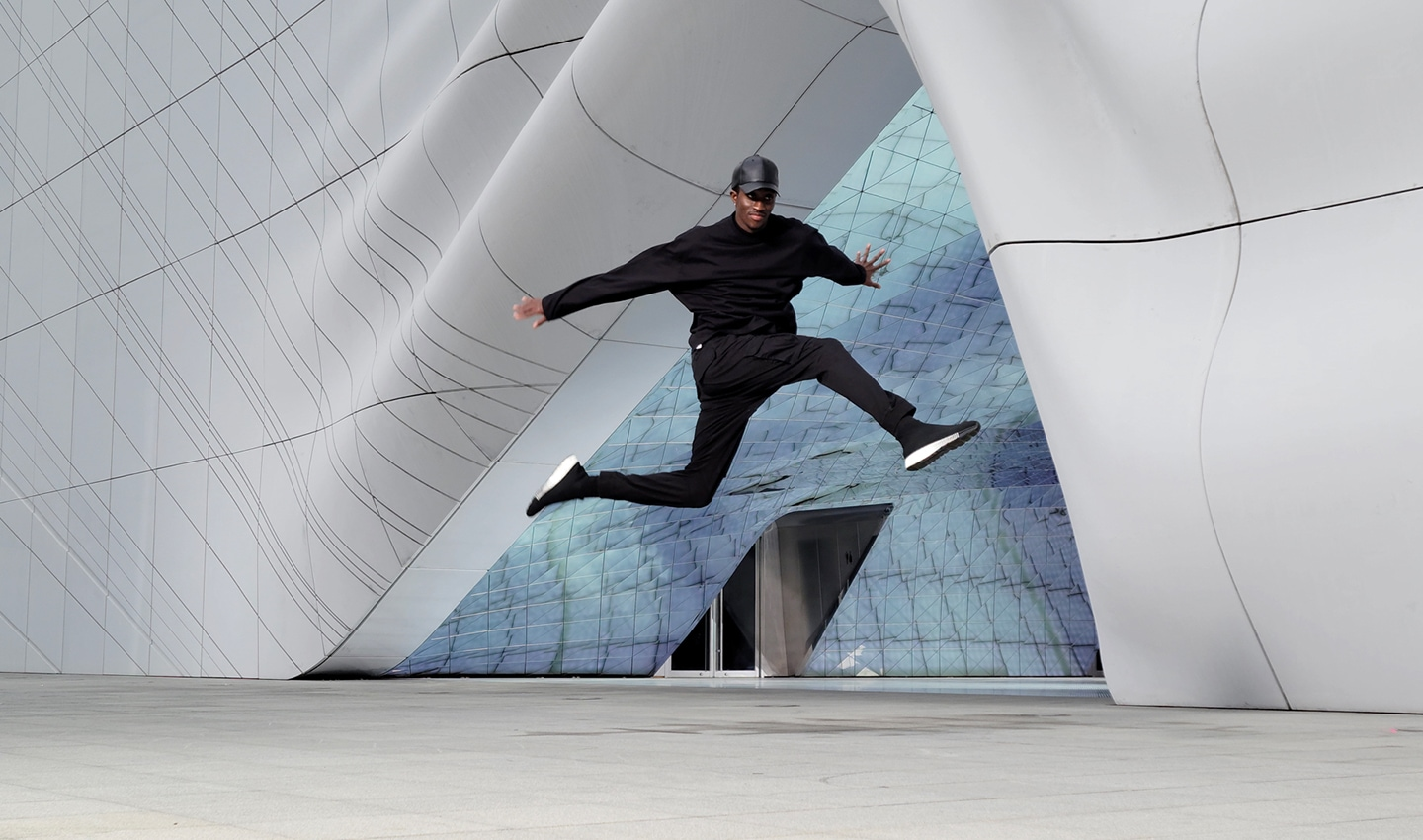 Scene of a man dancing in front of an architectural structure, shot with 8K on Galaxy S21 Ultra 5G. A still image is taken from the video using 8K Video Snap. The image shows how crisp a frame from 8K video looks as a photo.