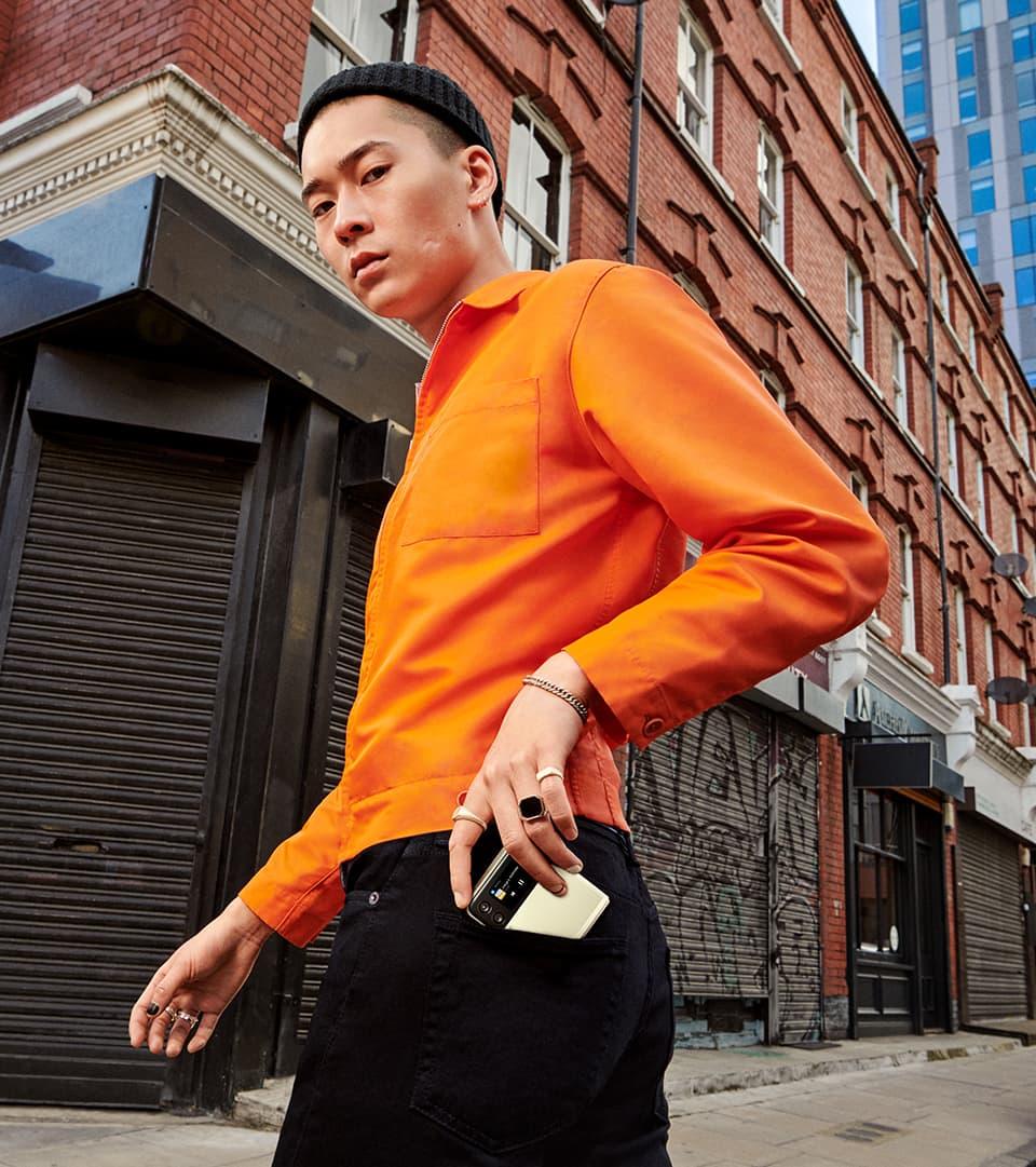 Un hombre está de pie mirando a la cámara. Está metiendo un Galaxy Z Flip3 5G en el bolsillo trasero de sus pantalones vaqueros.