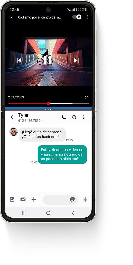 """Un Galaxy Z Flip3 5G desplegado en Multi Active Window, con un video de YouTube en la parte superior, un video llamado """"Ir en bicicleta por el centro"""" y una persona parada en una bicicleta sobre una rampa. La aplicación Mensajes en la parte inferior y el mensaje de texto recibido de Tyler dice: """"¡Llegó el fin de semana! ¿Qué estás haciendo?"""". El mensaje de texto enviado dice: """"Estoy viendo un video de viajes... y ahora quiero dar un paseo en bicicleta, jaja""""."""