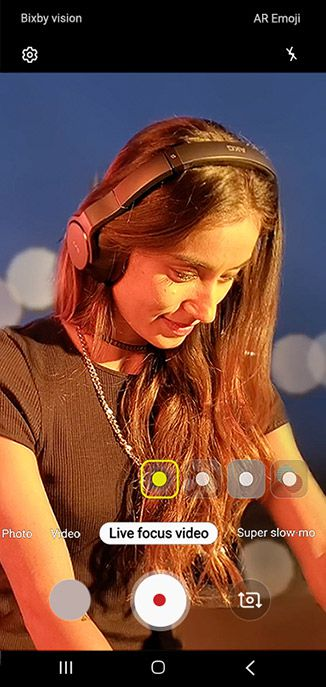 Camera GUI overlaid on top of a video being captured by Galaxy Note10 plus of a woman DJing