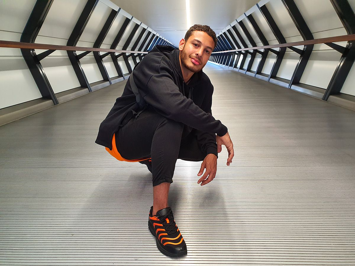 Photo captured by the Wide-angle Camera of a man squatting in the middle of a long hallway